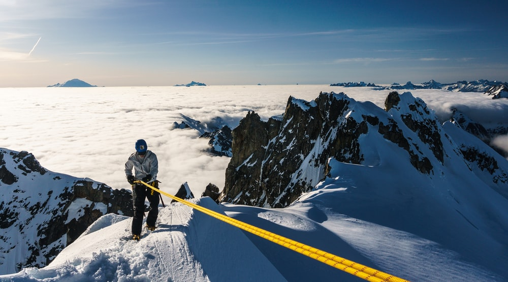man in black jacket and black pants standing on snow covered mountain during daytime