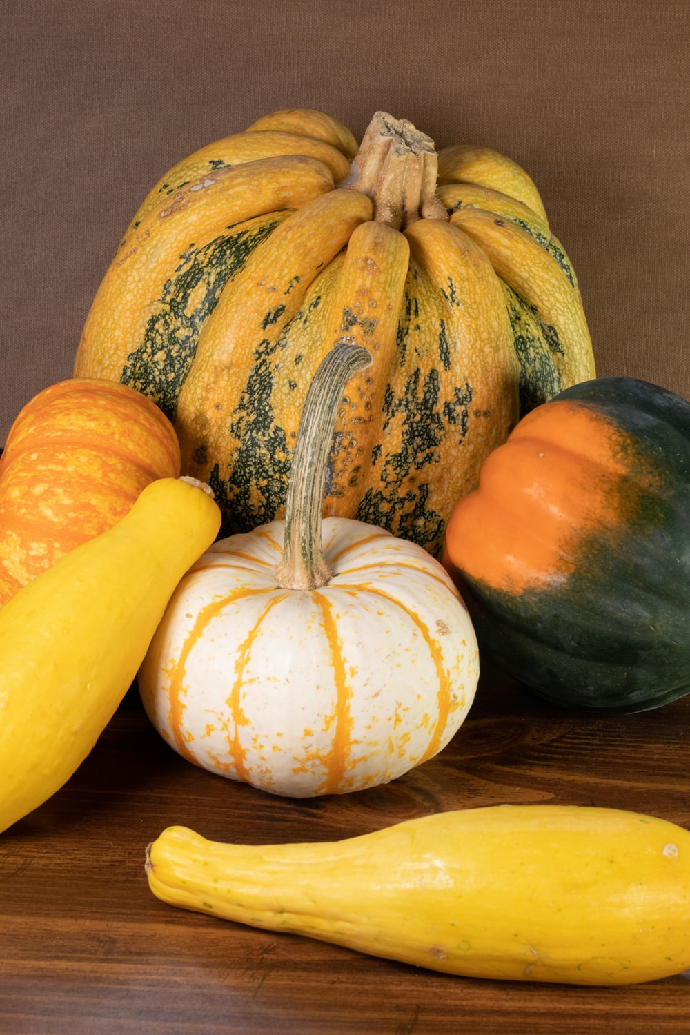 yellow and green pumpkin on brown wooden table