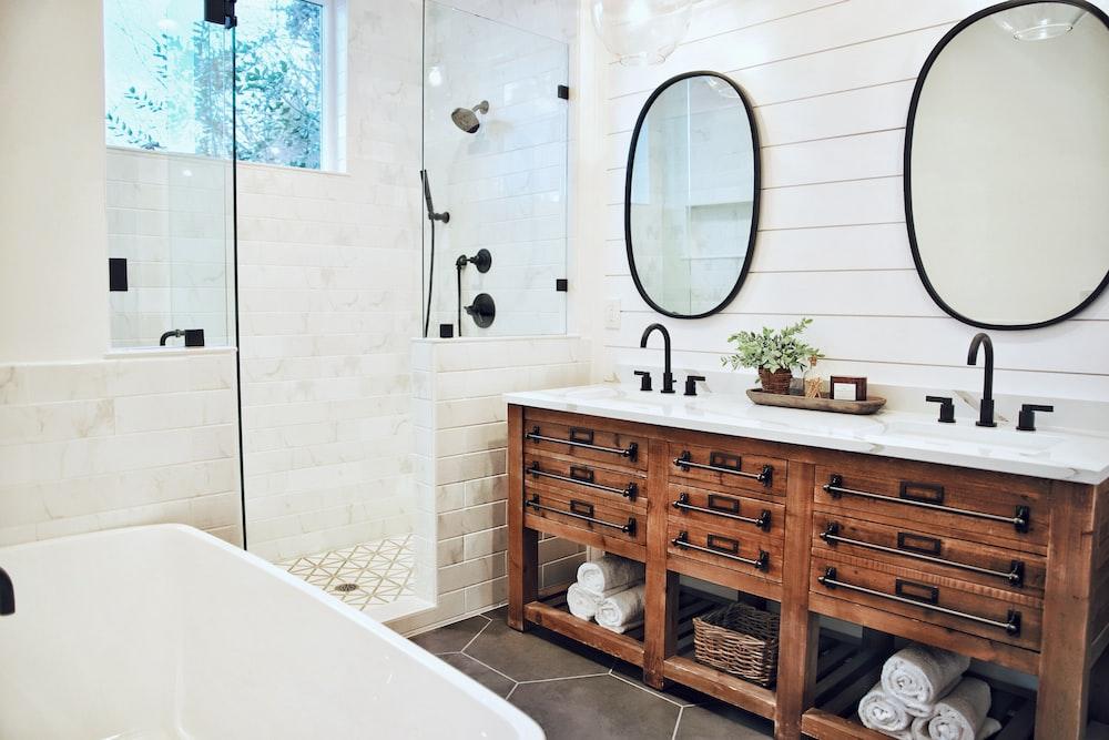 white ceramic bathtub near brown wooden cabinet