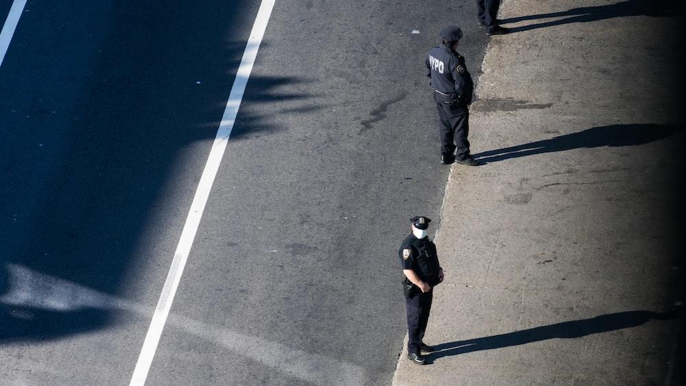 man in black shirt walking on gray asphalt road during daytime