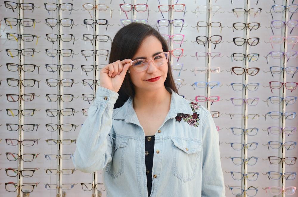 woman in blue denim jacket wearing eyeglasses