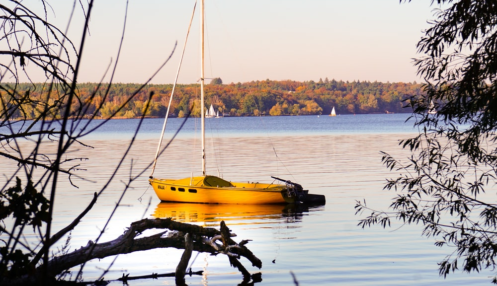 yellow and white boat on water during daytime