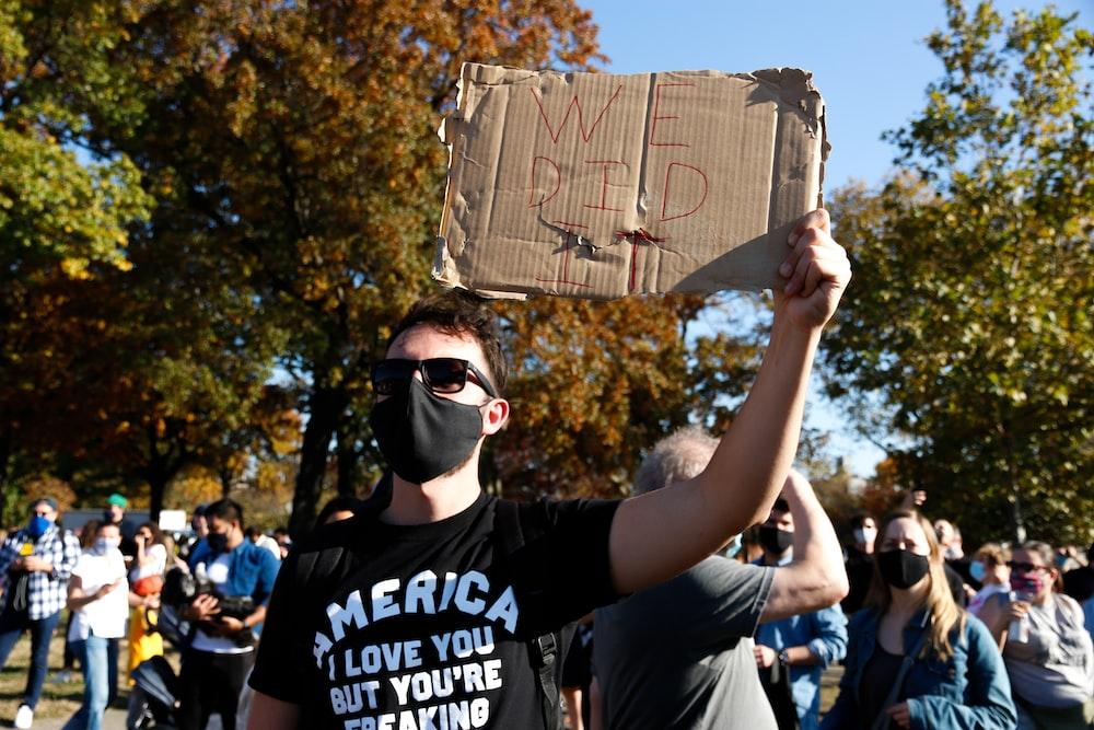 man in black crew neck t-shirt holding brown paper bag