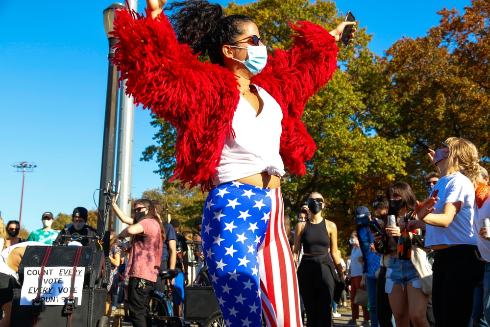 woman in red long sleeve shirt and blue white and red pants standing near people during