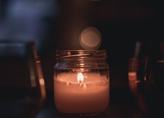 lighted candle in clear glass jar