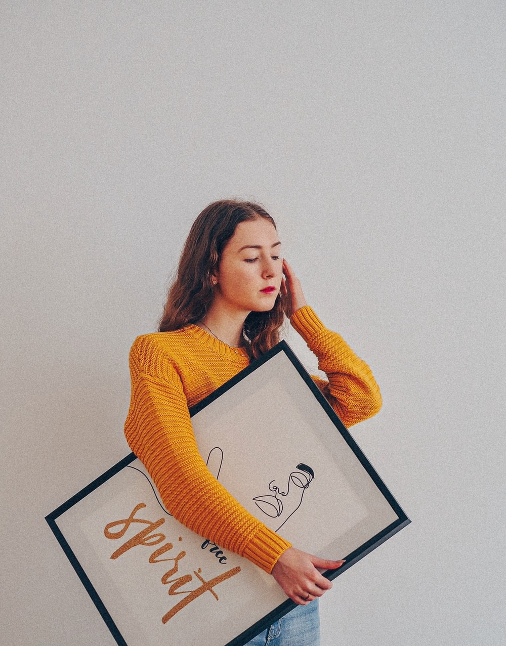 woman in yellow sweater holding black framed photo