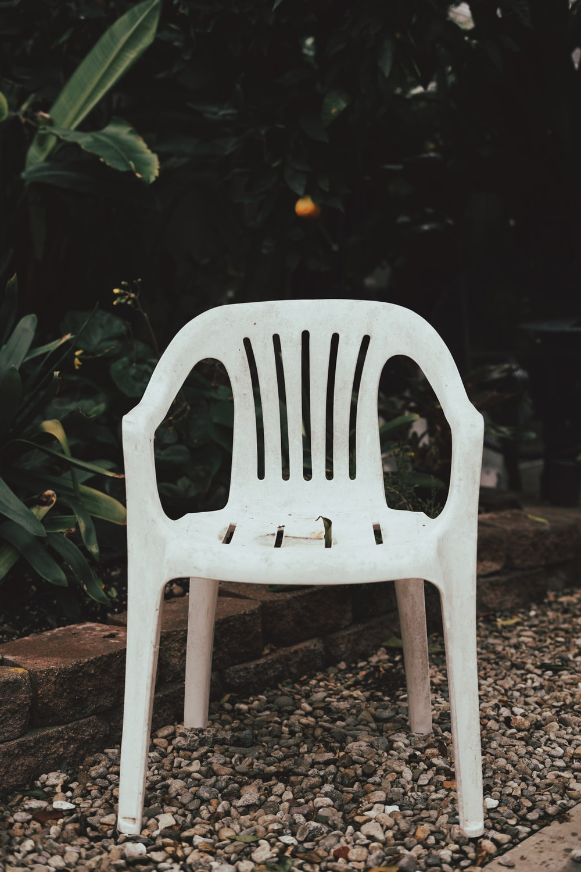white plastic chair on brown soil