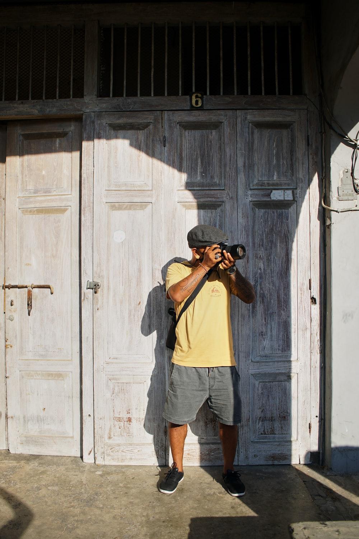 man in yellow t-shirt and blue denim shorts standing beside white wooden door