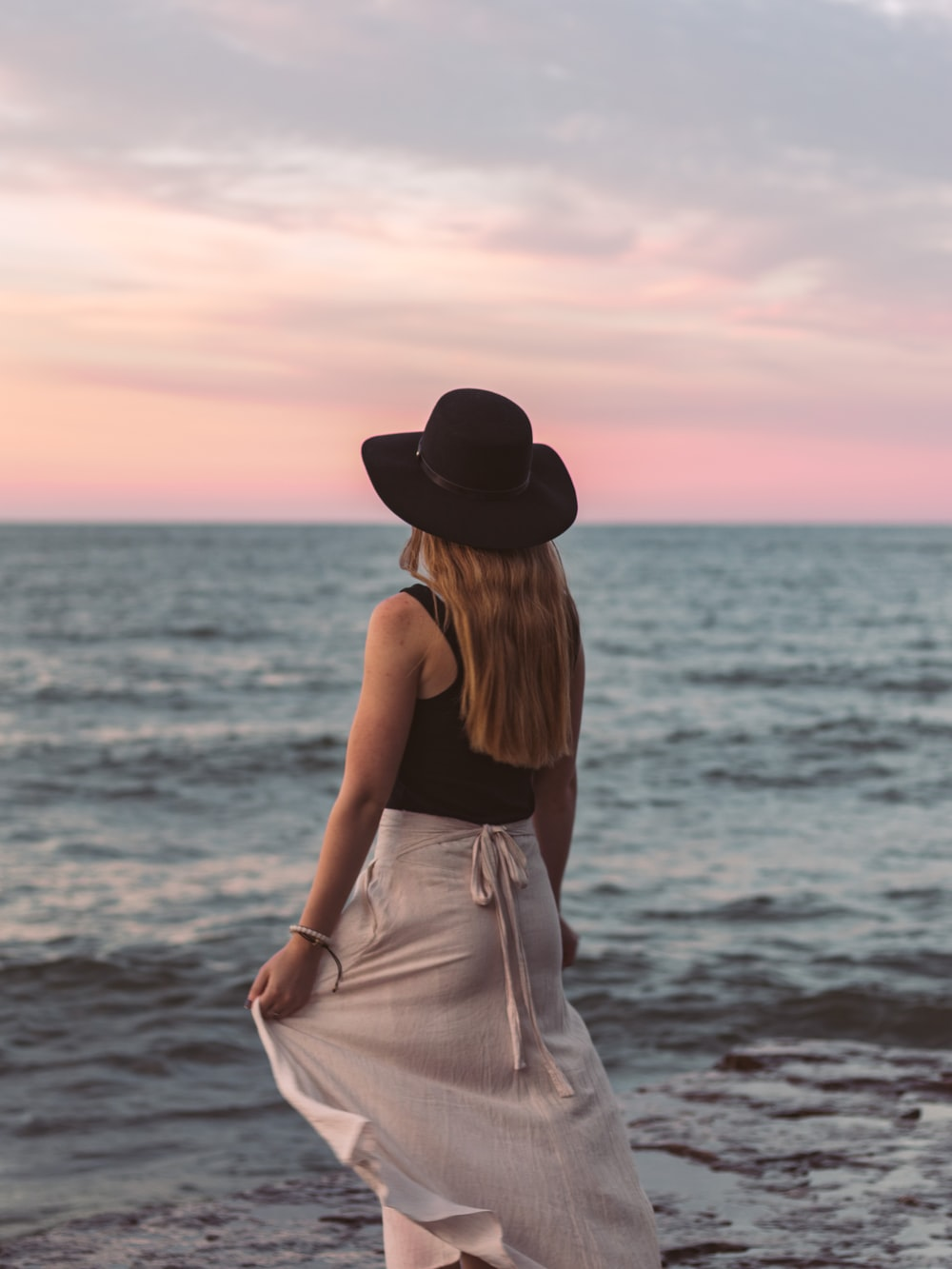 woman in black tank top and white skirt standing on seashore during daytime