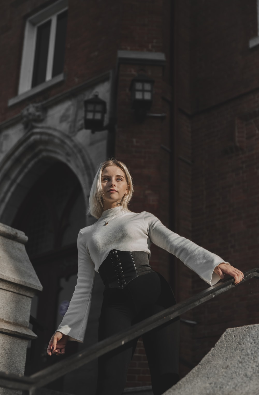 woman in white long sleeve shirt and black skirt standing on stairs
