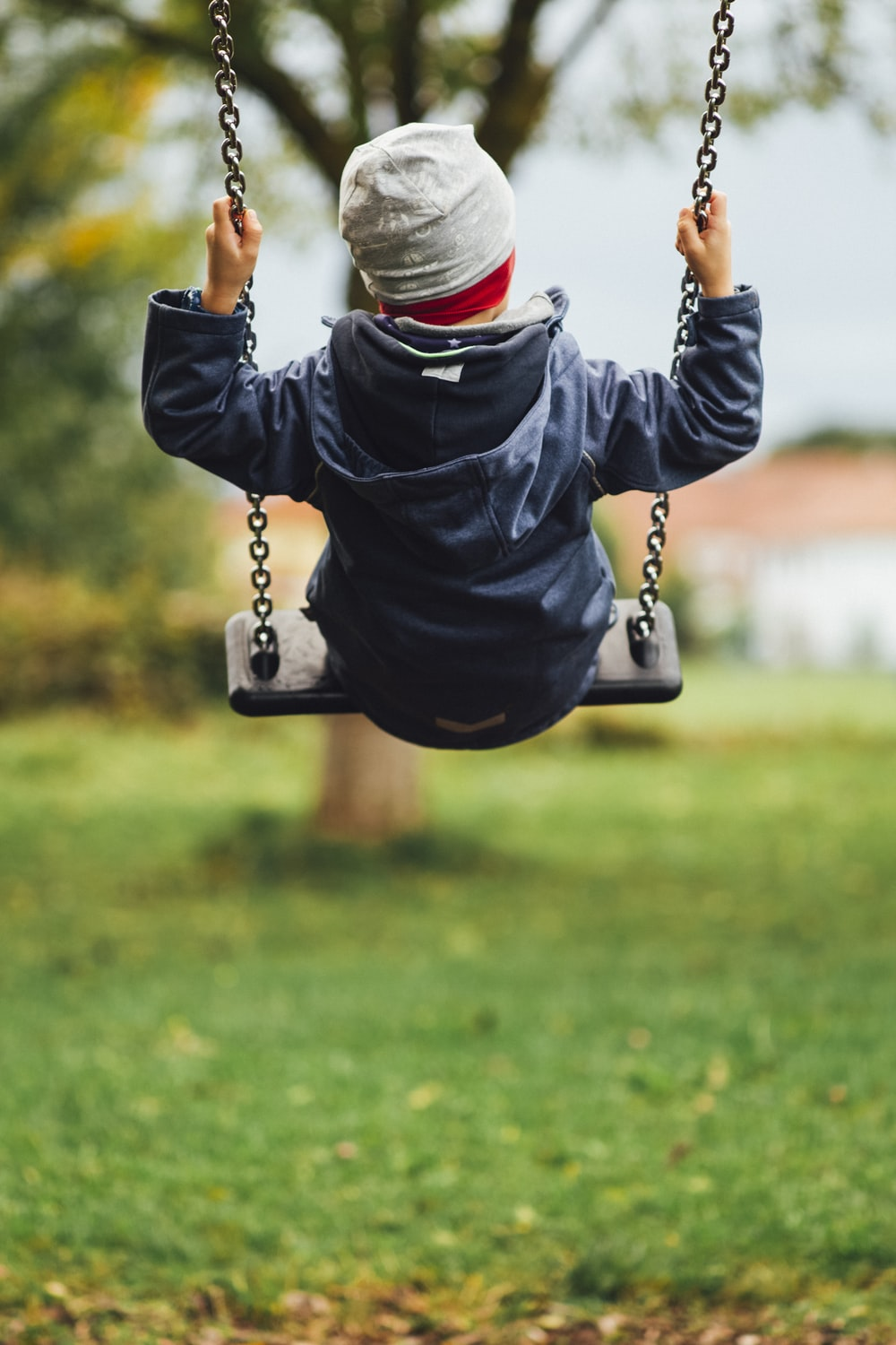 child in gray long sleeve shirt sitting on swing during daytime