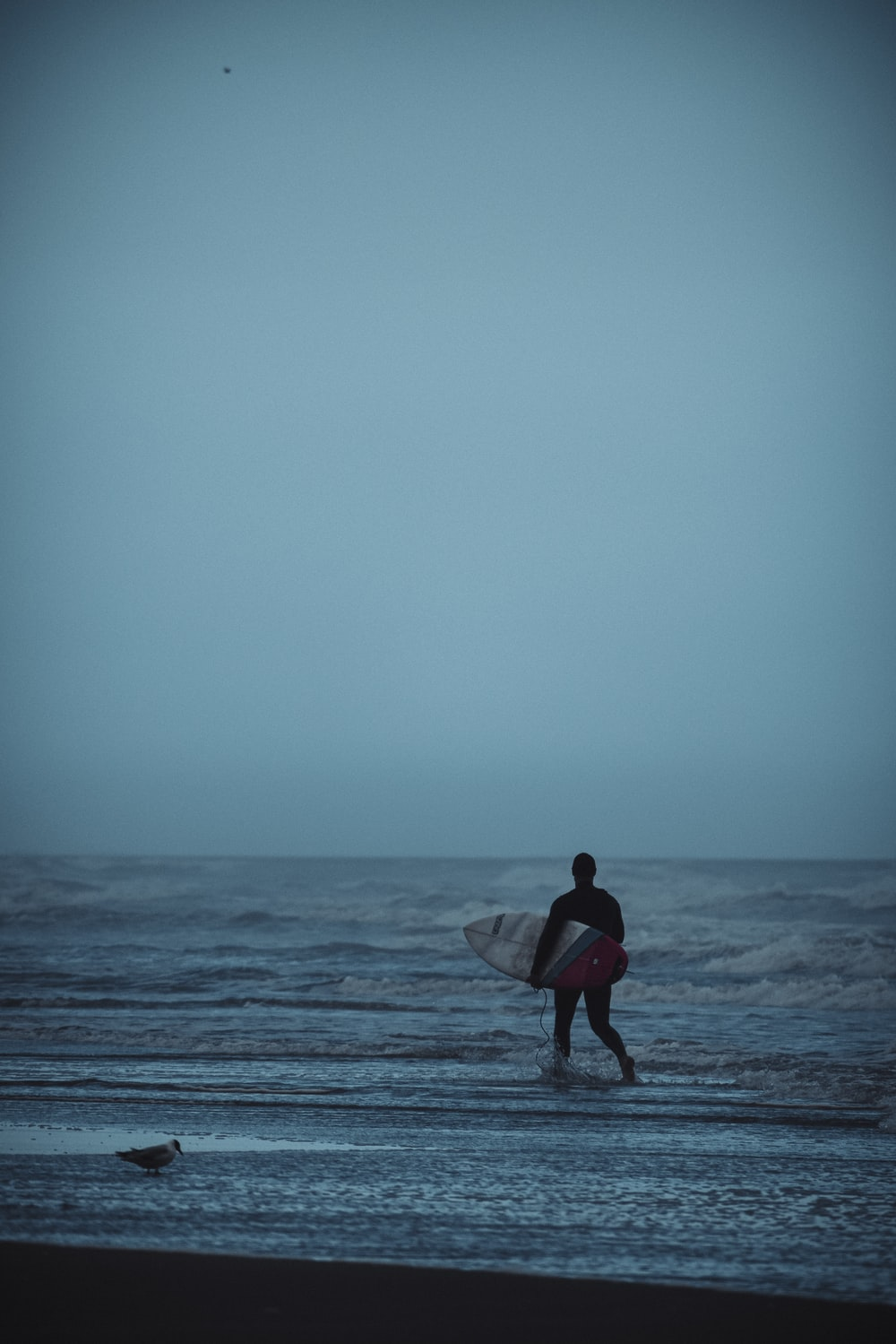man in red shirt holding white surfboard walking on beach during daytime