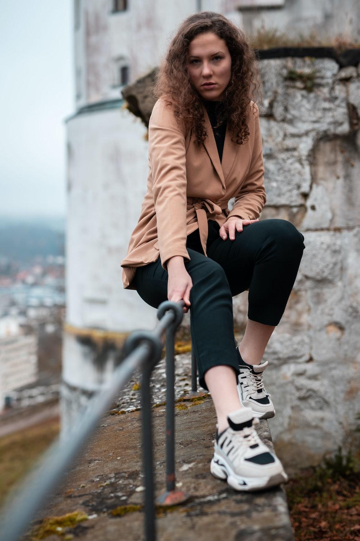 woman in brown coat sitting on gray metal railings during daytime