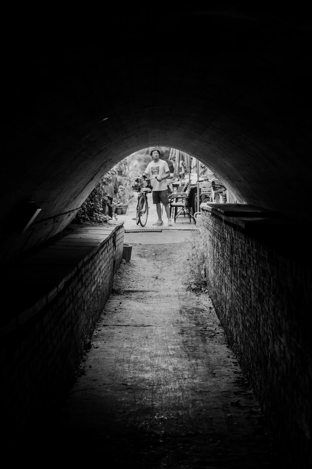 grayscale photo of people walking on tunnel