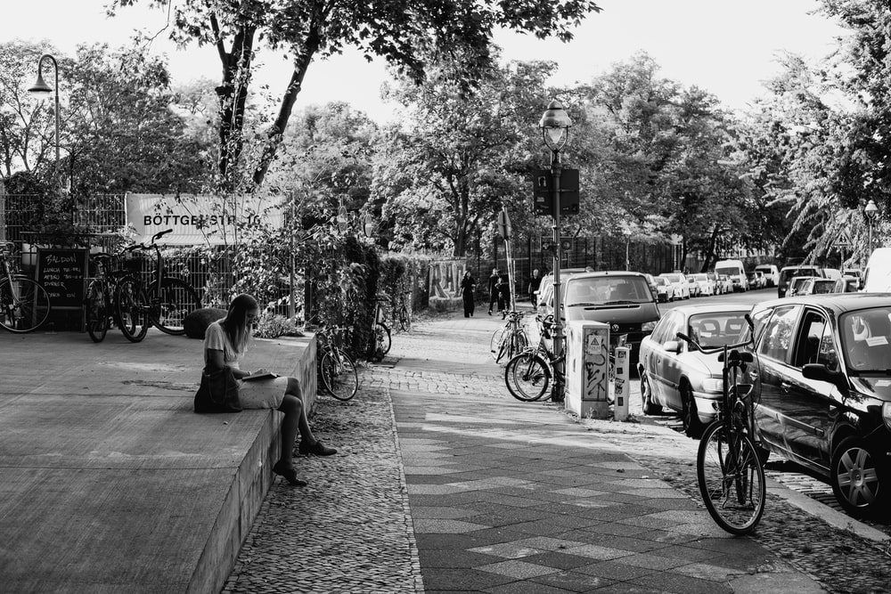 grayscale photo of man and woman sitting on bench near road
