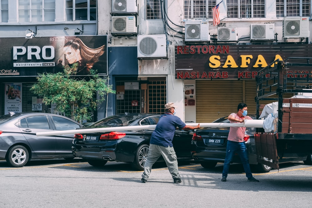 man in black jacket and blue denim jeans standing beside black sedan during daytime