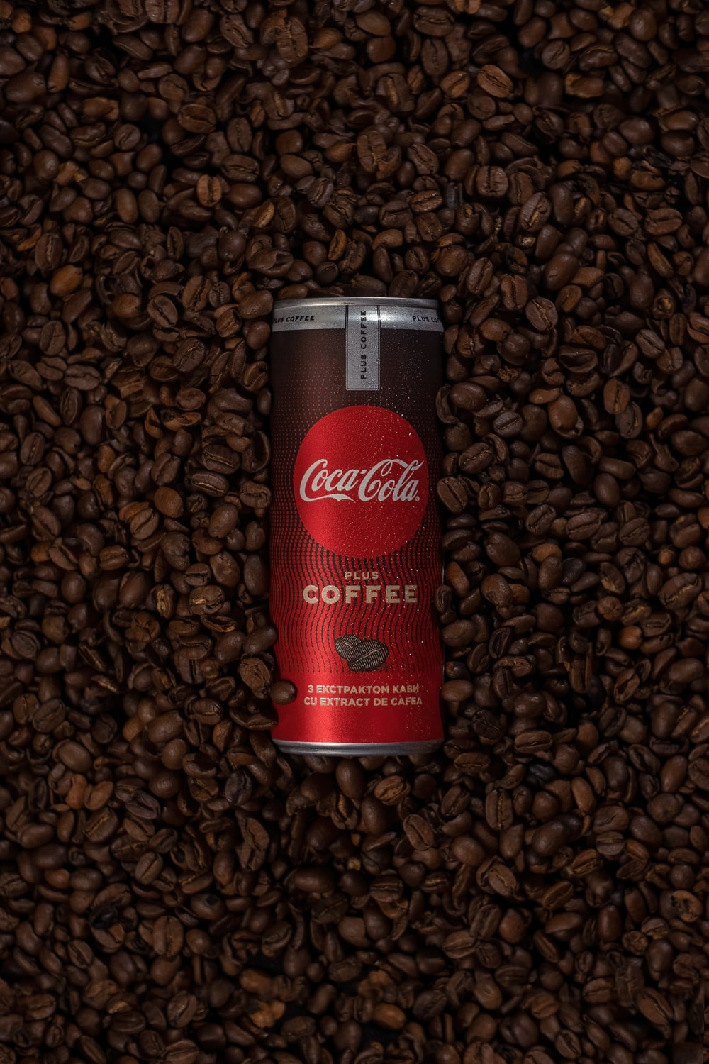 red coca cola can on brown coffee beans