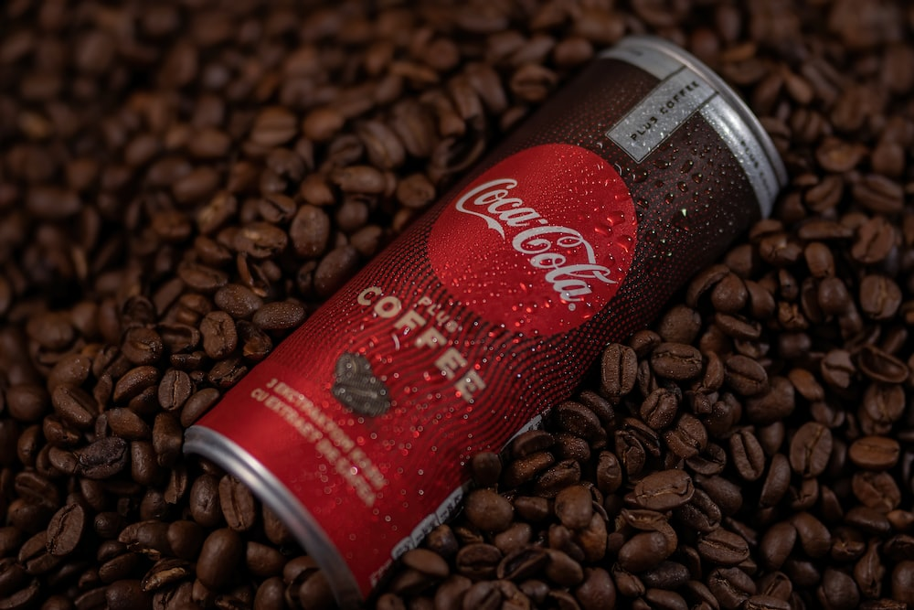 red and silver can on brown coffee beans