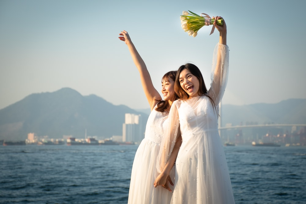 woman in white dress holding yellow and green leaf