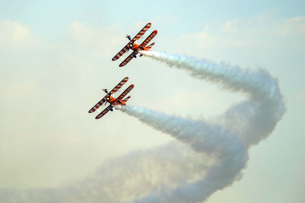 red and white plane flying on sky during daytime