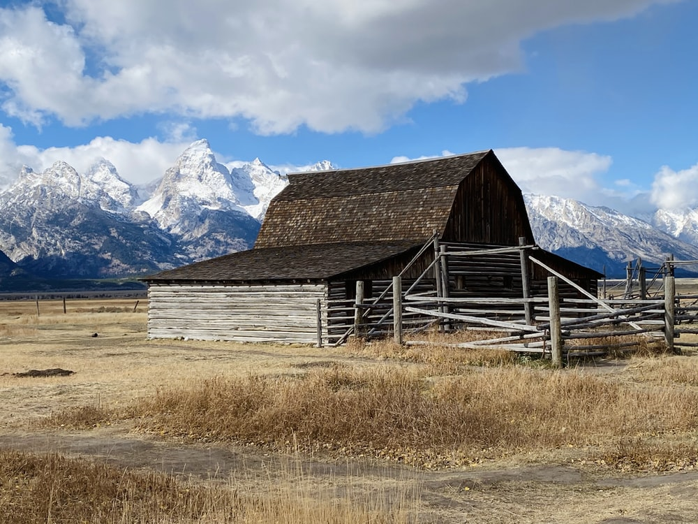 brown wooden barn on brown grass field near snow covered mountain under blue and white cloudy
