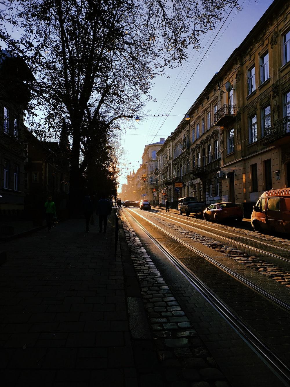people walking on sidewalk near train tracks during daytime