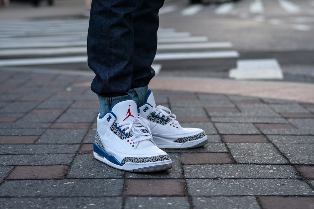person in blue denim jeans and white and blue nike sneakers