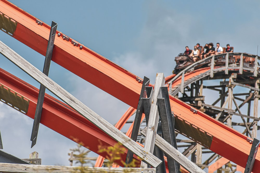 people riding red roller coaster during daytime