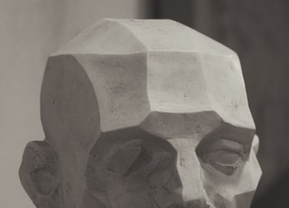 gray concrete face bust on white surface