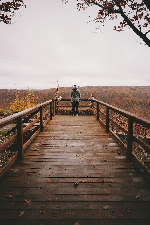 woman walking on wooden bridge during daytime