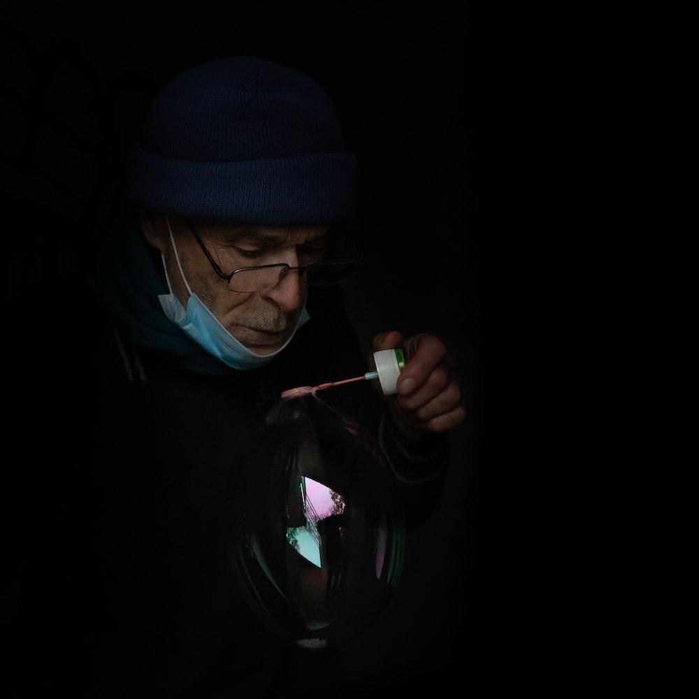 man in blue knit cap and black hoodie smoking cigarette