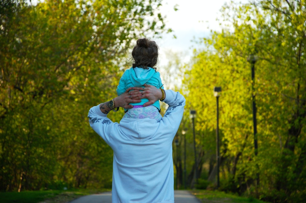 woman in white dress carrying baby in blue jacket