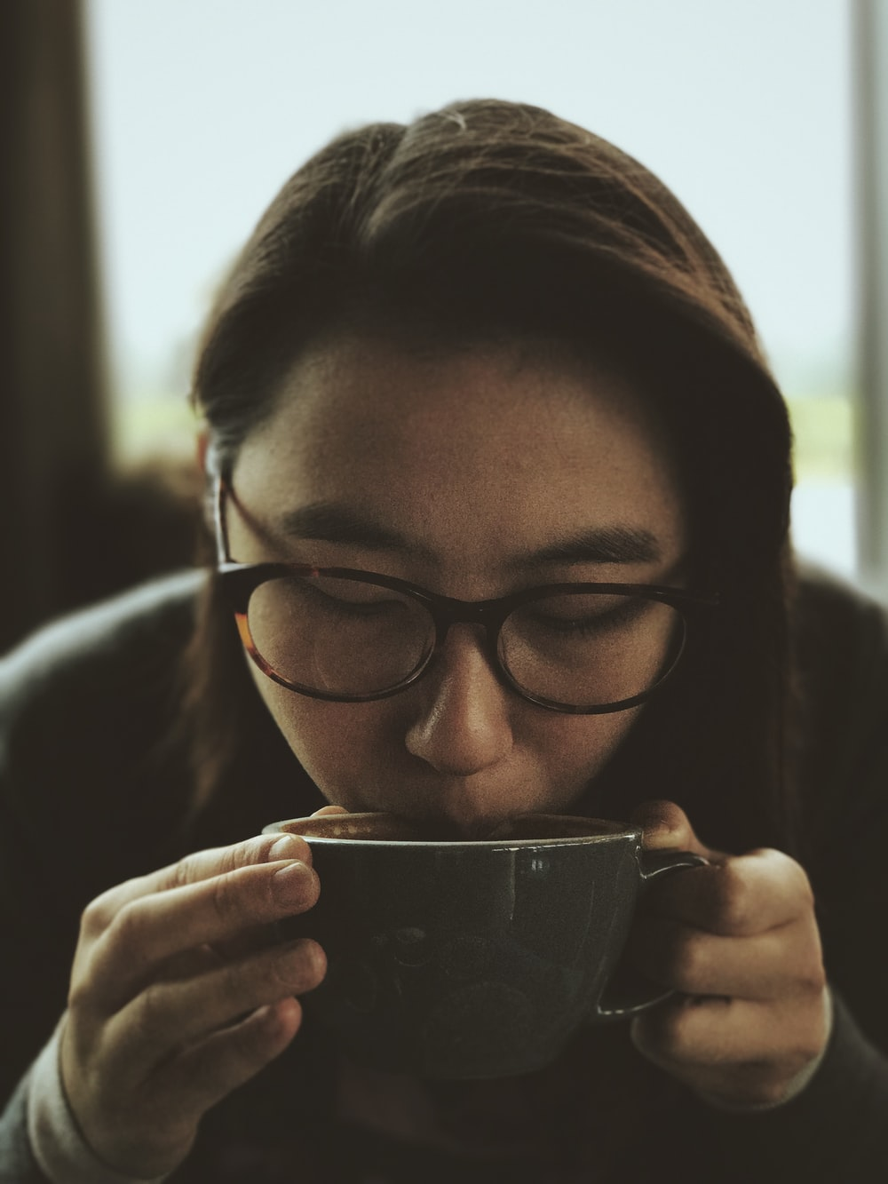 woman in black framed eyeglasses holding clear glass mug