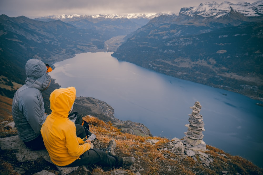 person in yellow hoodie sitting on rock formation looking at lake during daytime