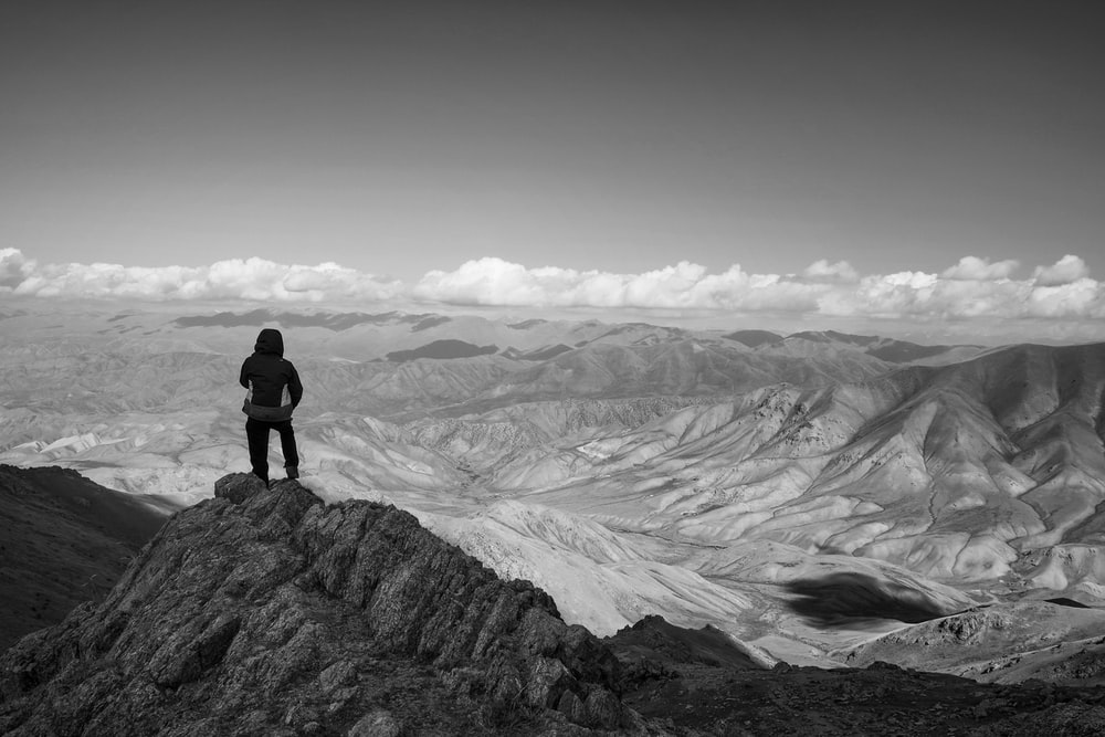 person standing on rock formation in grayscale photography