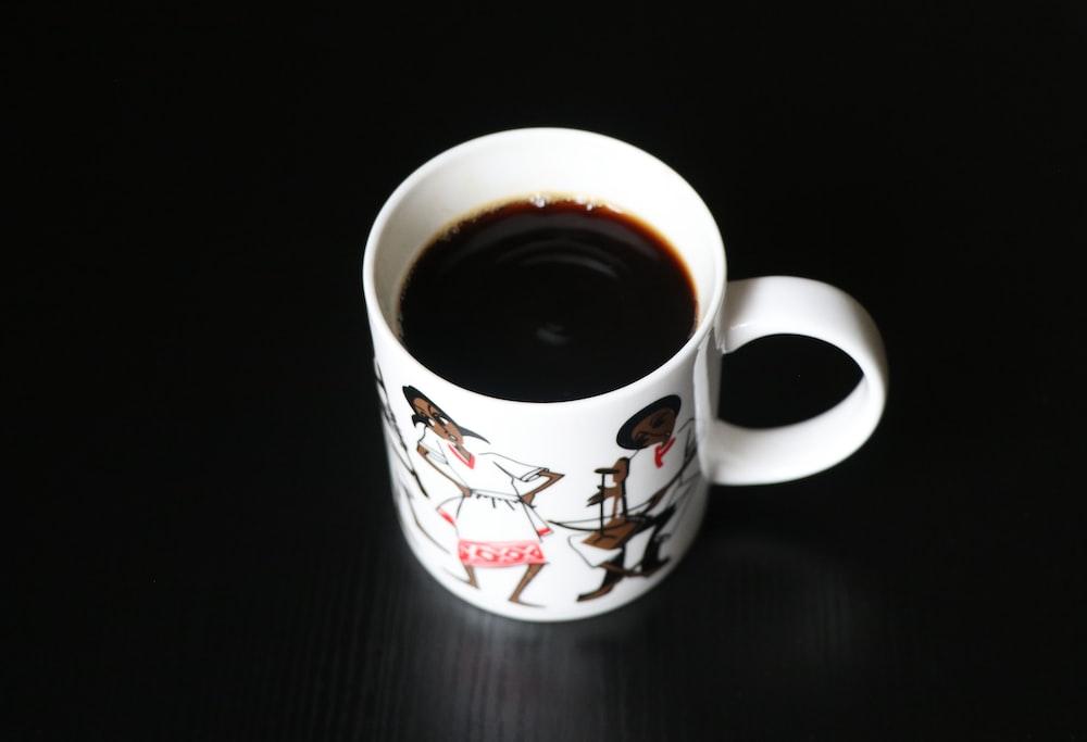 white and red ceramic mug with black liquid