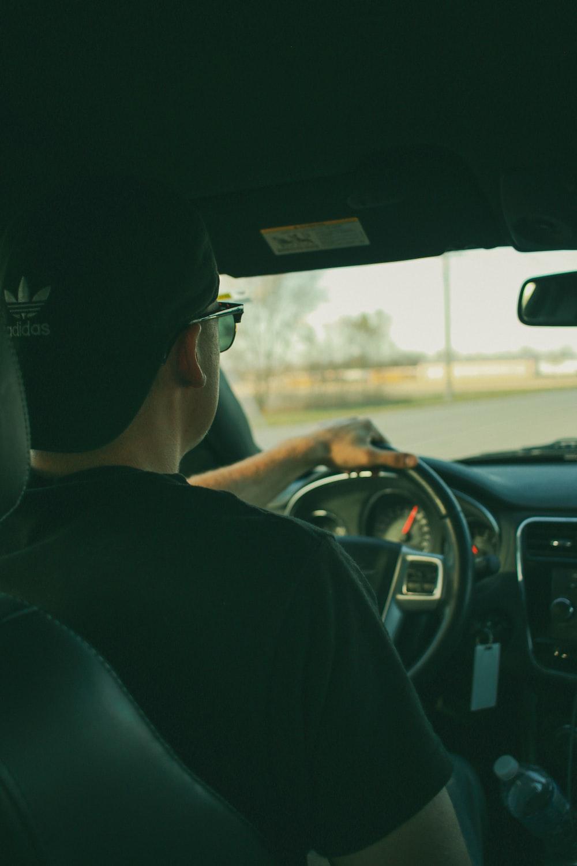 man in black shirt driving car during daytime