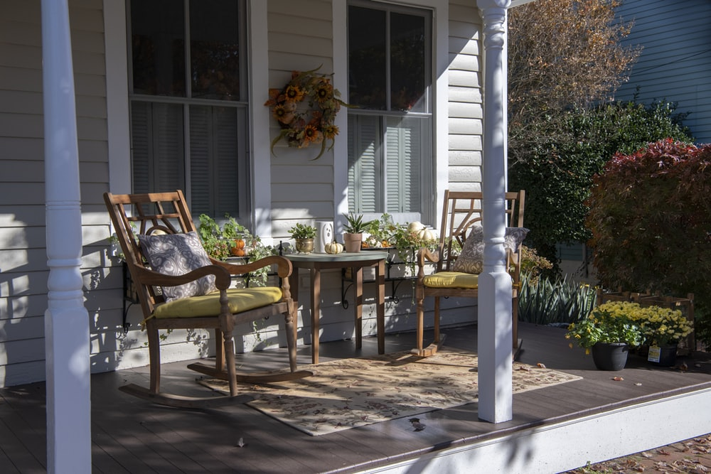 brown wooden chairs and table near white wooden post