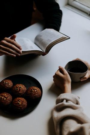Två personer läser Bibeln och fikar