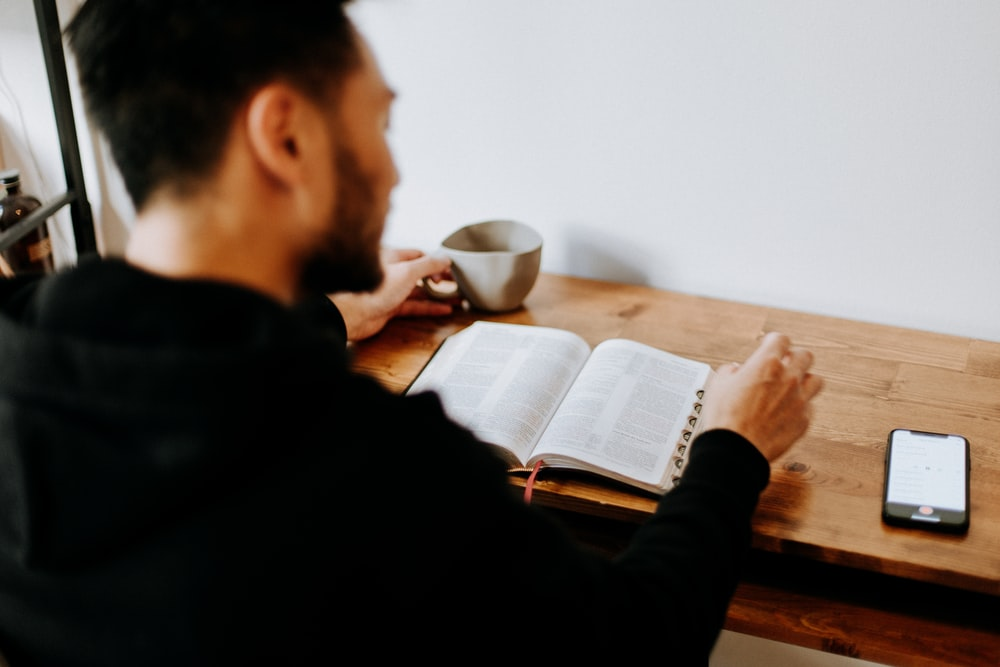 man in black long sleeve shirt writing on white paper