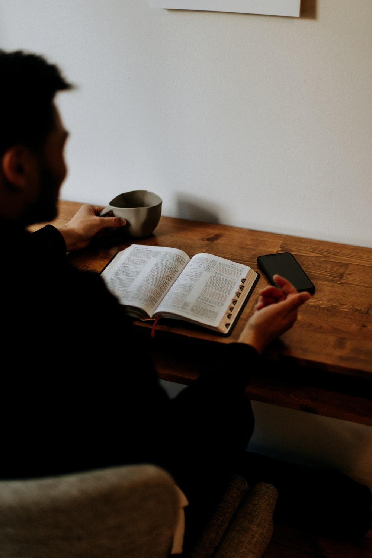 man in black shirt reading book