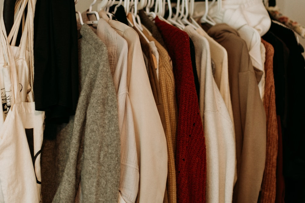 brown and white coat hanged on rack