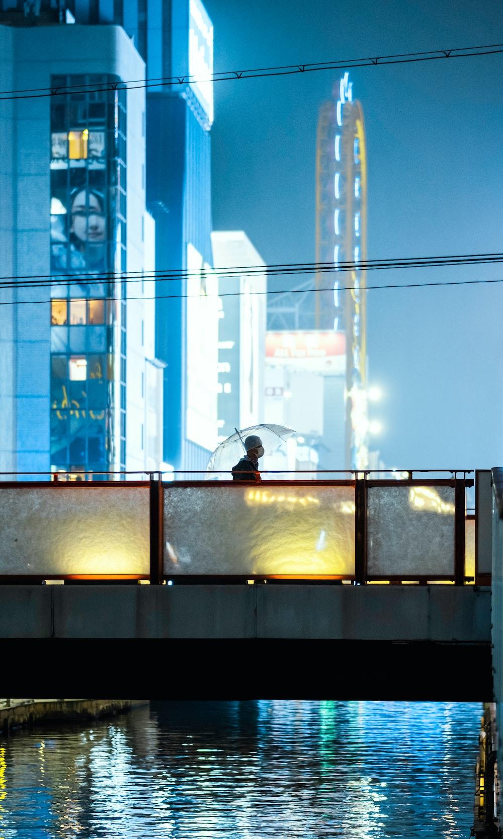 person in black jacket standing near glass window