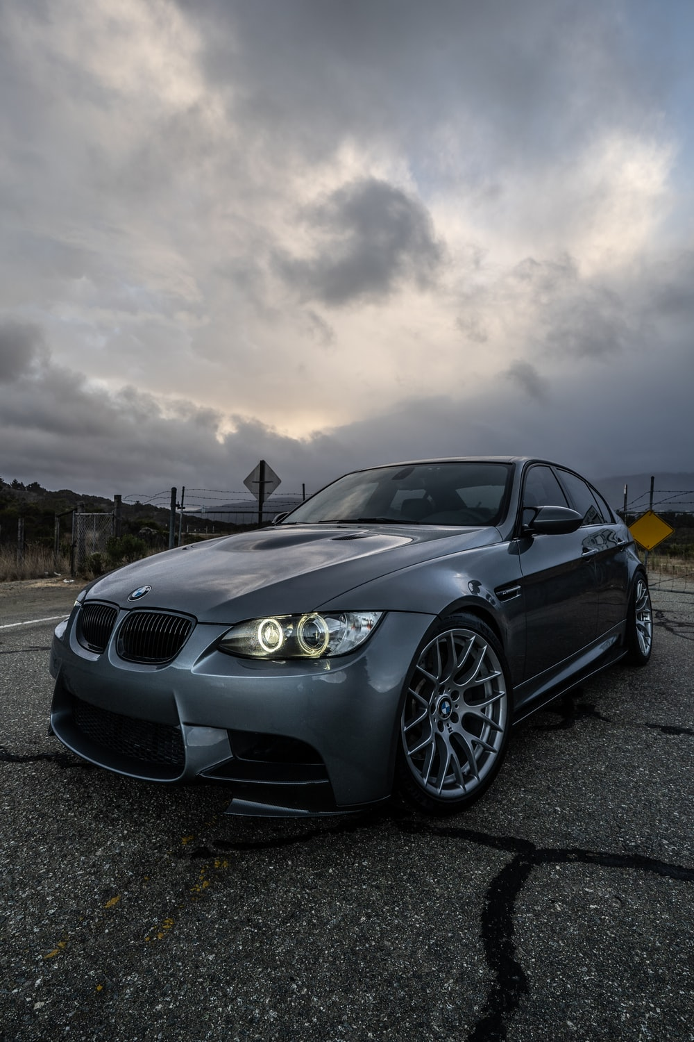 black bmw m 3 coupe on road under gray clouds