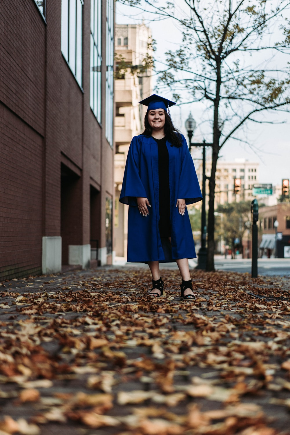woman in blue academic dress standing on brown dried leaves during daytime