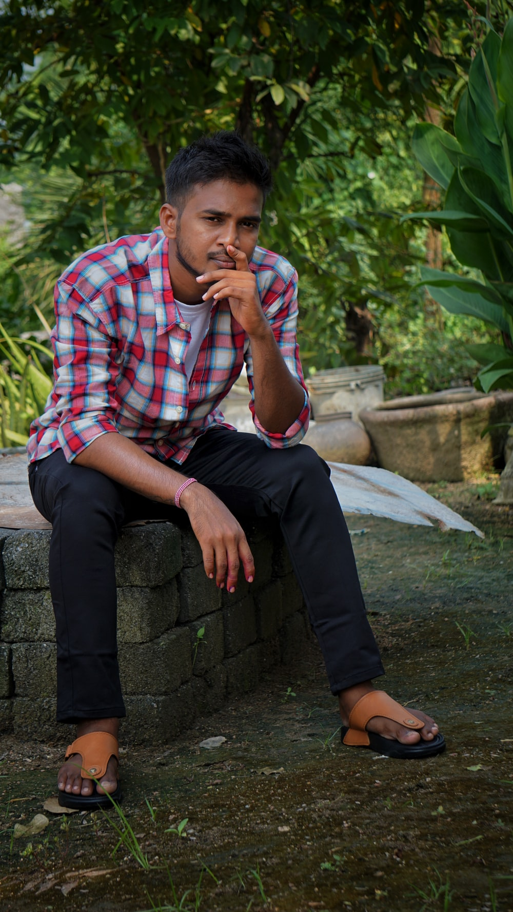 man in red white and blue plaid button up shirt sitting on concrete bench
