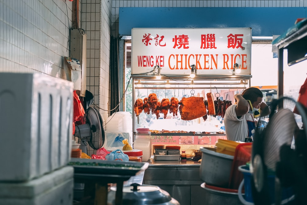man in white t-shirt standing in front of food stall