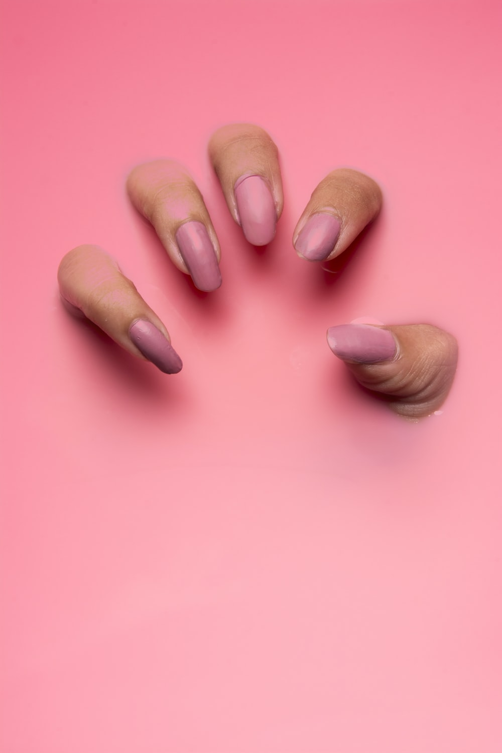 persons hand on pink surface