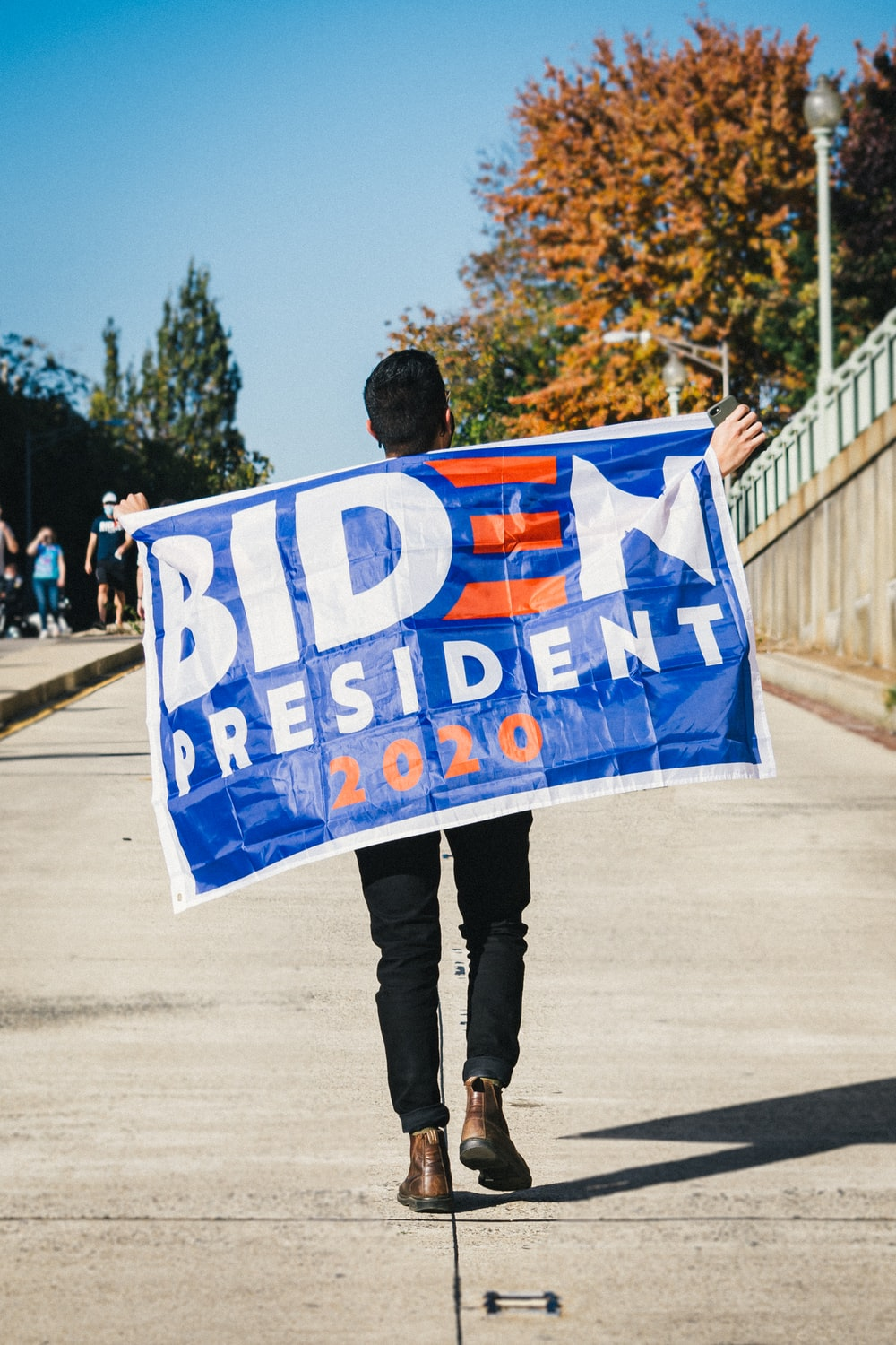 man in black jacket holding blue and white banner