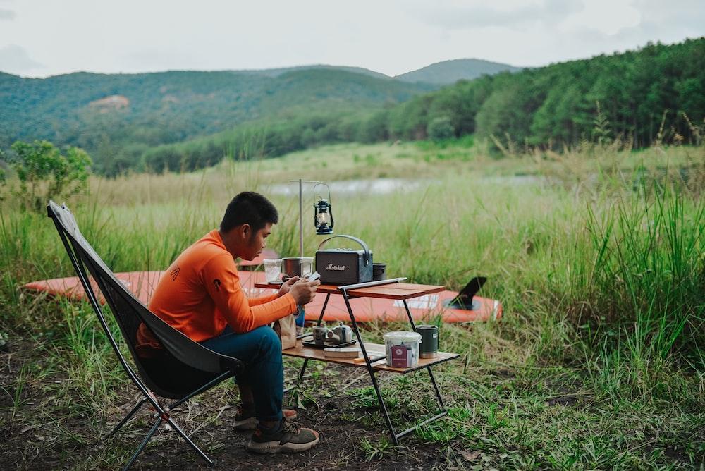 man in orange shirt sitting on black camping chair